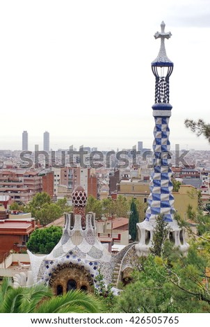 BARCELONA, SPAIN - CIRCA OCTOBER 2013: Blue and white checked column rising from the top of one of the entrance pavilions in Park Guell, with the city of visible beyond, seen from the terrace