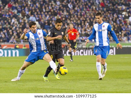 BARCELONA, SPAIN - JANUARY 8: Alexis Sanchez (middle) of FCB in action during the Spanish league match between RCD Espanyol and FC Barcelona, final score 1-1, on January 8, 2012, in Barcelona, Spain. - stock photo