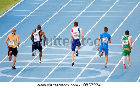 BARCELONA, SPAIN - JULY 27: Christophe Lemaitre (center) competes on the Men 100 m during the 20th European Athletics Championships at the Olympic Stadium on July 27, 2010 in Barcelona, Spain. - stock photo
