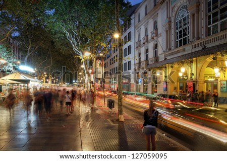 BARCELONA, SPAIN - JULY 31: Crowded La Rambla street at the heart of Barcelona, Spain at night time with the Liceu Theater on the right on July 31, 2013.