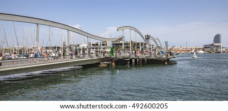 BARCELONA, SPAIN - JULY 4, 2016: Marina Port Vell and the Rambla del Mar in Barcelona. Ramblas del Mar are a wooden bridge built in 1994.