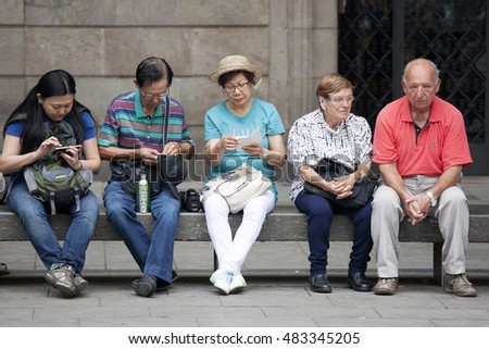 Barcelona, Spain - July 25, 2016 : Tourists sitting at bus stop waiting for the bus.