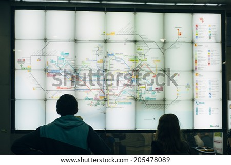 BARCELONA, SPAIN - JULY 13: Two commuters observes a board with the map of Metro Barcelona on July 13, 2014 in Sants train station in Barcelona, Spain.