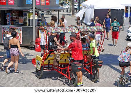 BARCELONA, SPAIN - JULY 31, 2015: Two young men and rickshaw taxis in Barcelona. Rickshaw taxis offer unique group tours through the city and a funny form of transport among locals and tourists. - stock photo