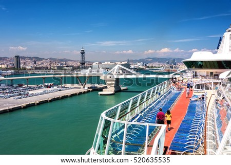 BARCELONA, SPAIN - JUNE 7, 2016:  Cruise ship passengers stroll around the Lido Deck on a cruise ship anchored in port in Barcelona, Spain.