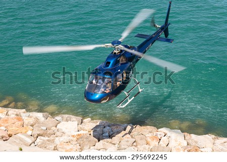 BARCELONA, SPAIN - JUNE 27. Helicopter above the harbor of Barcelona on June 27, 2015. The rotorcraft offers Helicopter tours to sightseeing above Barcelona. The Heliport is in the marina Port Vell - stock photo