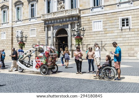 Barcelona,Spain - June 17, 2015: People walking and a tricycle with Desigual advertising in Sant Jaume square, in front of the facade of Generalitat of Catalonia