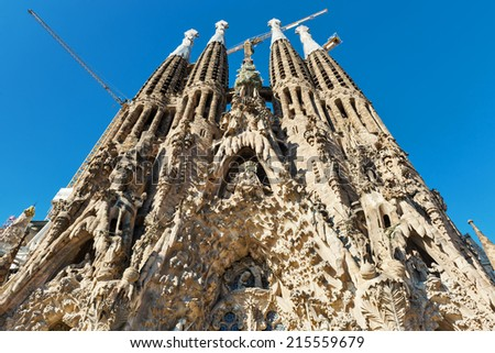 BARCELONA, SPAIN - JUNE 1, 2014: The Basilica of La Sagrada Familia against blue sky. Designed by Antoni Gaudi, its construction began in 1882 and is not finished yet.  - stock photo