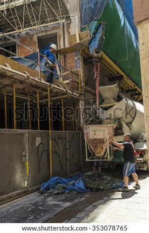 Barcelona, Spain - June 4, 2015: Workers running a construction crane is lifting a container of cement in the construction of a building in the old town of Barcelona