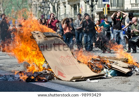 BARCELONA, SPAIN - MARCH 29: One of the multiple fires caused by heavy riots during nationwide spanish general strike against labour reforms in the city center of Barcelona on March 29, 2912. - stock photo