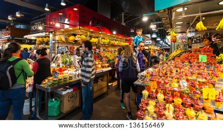 BARCELONA, SPAIN - MARCH 28: Vendors at La Boqueria market in March 28, 2013 in Barcelona, Spain.  The market is famous for its variety of fresh produce