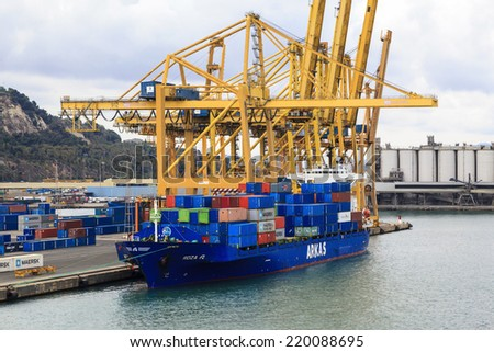BARCELONA SPAIN - MAY 19, 2014: Cargo ships docked for loading in industrial port quay of Barcelona one of the largest on the Mediterranean and the biggest in Spain. - stock photo