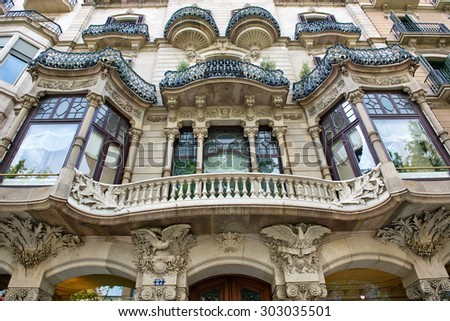 BARCELONA, SPAIN - MAY 02:Detail of an Art Nouveau building facade in Barcelona, Spain with a curved balcony between symmetrical windows and ornate stone carving. May 02, 2015 in Barcelona Spain - stock photo