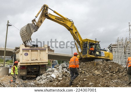 Barcelona, Spain - 12 May, 2014: excavator placing sand or debris on a truck - stock photo
