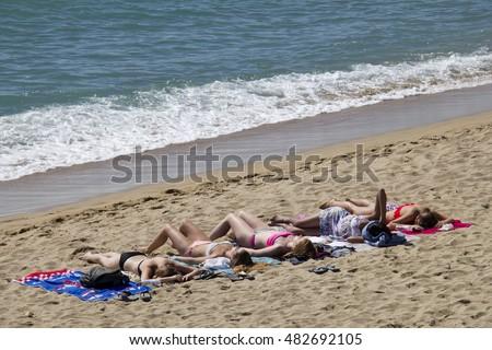 Barcelona, Spain - May 23, 2015: Girls lie suntanning on the beach in Barcelona, Spain on May 23, 2015.