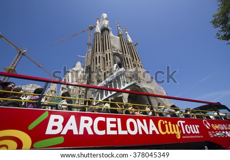 Barcelona, Spain - May 26, 2015: People sit on a double decker tourist coach in front of the Sagrada Familia Gaudi cathedral, on May 26, 2015 in Barcelona, Spain - stock photo