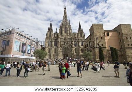 Barcelona, Spain - May 24, 2015: People walk around and take pictures on the Placa Nova square in front of the cathedral of Barcelona, Spain on May 23, 2015.