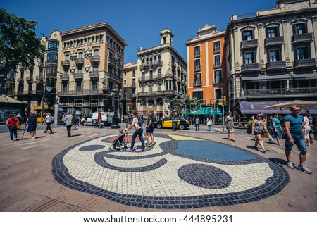 Barcelona, Spain - May 26, 2015. People walks at famous La Rambla Street. View with Pla de l'Os mosaic created by Joan Miro and House of Umbrellas.