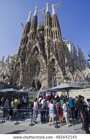 Barcelona, Spain - May 26, 2015: Tourists admire the construction of the Sagrada Familia cathedral of Barcelona, Spain on May 26, 2015.
