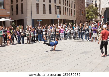 Barcelona, Spain-May25, 2013. Young men perform acrobatic dance routines for cash in front of locals and tourists on the streets of Barcelona, Spain - stock photo