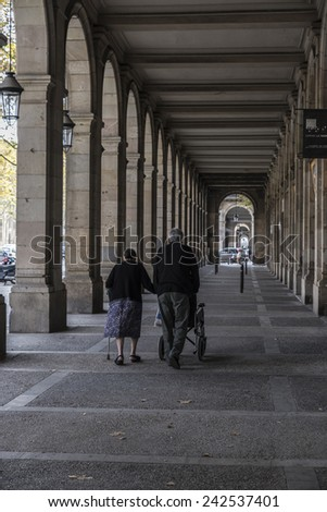 Barcelona, Spain - November 2, 2014: An elderly couple walks under the arches of Passeig Picasso. - stock photo