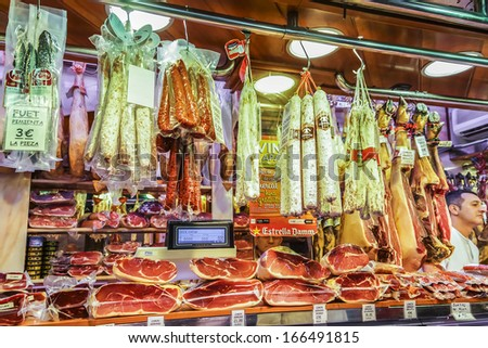 BARCELONA, SPAIN - NOVEMBER 16, 2013: Famous La Boqueria market - one of the oldest markets (Established in 1217) in Europe that still exist. A huge selection of traditional Spanish meat products. - stock photo
