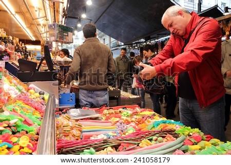 BARCELONA, SPAIN - NOVEMBER 6, 2012: People visit Boqueria market in Barcelona, Spain. Tripadvisor says it is best shopping destination in Barcelona, the most visited city in Spain. - stock photo