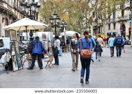 BARCELONA, SPAIN - NOVEMBER 6, 2012: Tourists walk famous Rambla street in Barcelona, Spain. According to Mastercard, Barcelona is the 15th most visited city worldwide (7.5m in 2012). - stock photo