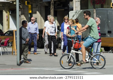 BARCELONA, SPAIN - OCTOBER 7, 2014: A man riding her bicycle, stroll along one of the busiest streets of the city, next to a city bus stand. - stock photo