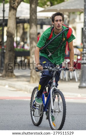 BARCELONA, SPAIN - OCTOBER 6, 2014: A man riding her bicycle, stroll along one of the busiest streets of the city, next to a city bus stand. - stock photo