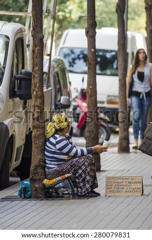 BARCELONA, SPAIN - OCTOBER 7, 2014: A woman sitting on the floor, asking alms coins in one of the streets of their city. - stock photo