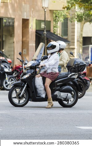 BARCELONA, SPAIN - OCTOBER 7, 2014: A young woman, riding a motorcycle, wait until the light turns green, on a city street. - stock photo