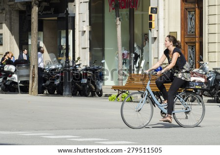BARCELONA, SPAIN - OCTOBER 7, 2014: A young woman riding her bicycle, stroll along one of the busiest streets of the city, next to a city bus stand. - stock photo