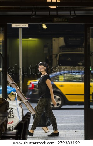 BARCELONA, SPAIN - OCTOBER 6, 2014: A young woman walks through one of the busiest streets in the city. - stock photo