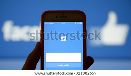 BARCELONA, SPAIN - SEP 29, 2015: Hand holding a mobile phone and using the social network Facebook application. - stock photo