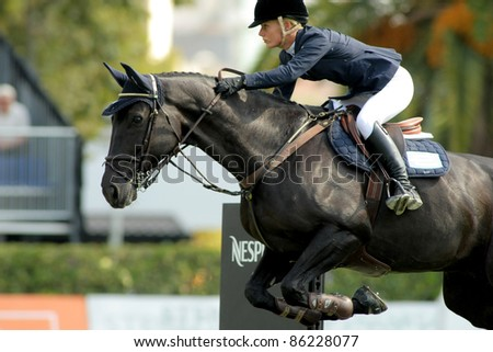 BARCELONA, SPAIN - SEPT, 23: Angelica Augustsson in action rides horse Walter 61 during the 100th CSIO event at the Real Club de Polo Barcelona on September 23, 2011 in Barcelona, Spain - stock photo