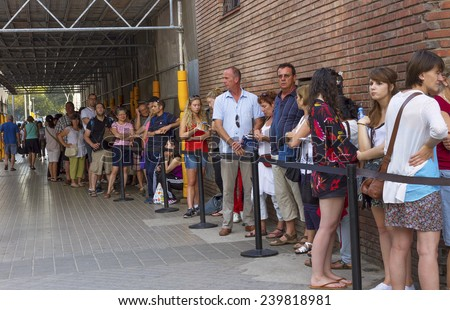 BARCELONA, SPAIN-SEPTEMBER 18: Long queue of people for ticket to La Sagrada Familia - designed by Gaudi, which is being build in1882 and is not finished yet September 18, 2014 in Barcelona, Spain. - stock photo