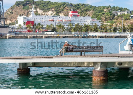 BARCELONA, SPAIN - SEPTEMBER 15. Man is sunbathing on a bench of the Rambla Del Mar in Barcelona on September 15, 2016. The harbor with the ferry to Mallorca and the Montjuic are in the background