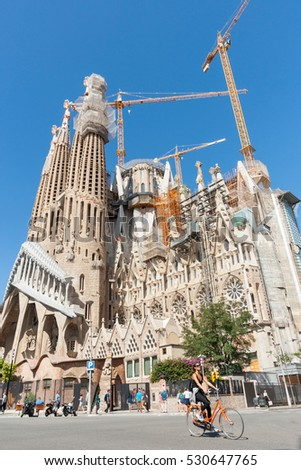 BARCELONA, SPAIN - SEPTEMBER 18; Sagrada Familia, Gaudi's most famous and uncompleted church cranes working while girl on bicycle passes in street below September 18, 2016,  in Barcelona, Spain