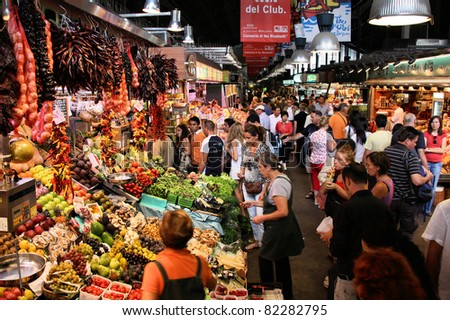 BARCELONA, SPAIN - SEPTEMBER 13: Tourists in famous La Boqueria market on September 13, 2009 in Barcelona. One of the oldest markets in Europe that still exist. Established 1217. - stock photo