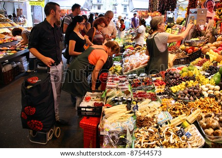 BARCELONA, SPAIN - SEPTEMBER 13: Tourists shop in famous La Boqueria market on September 13, 2009 in Barcelona, Spain. One of the oldest markets in Europe that still exist. Established 1217. - stock photo