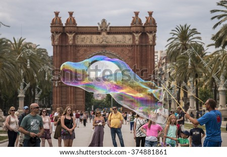 BARCELONA, SPAIN: 24st MAY, 2015: Pedestrians watch a soap bubble performer in of the amazing Arc de Triomf, located in Barcelona, Spain.