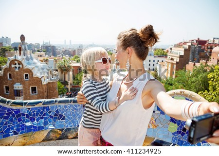 Barcelona will show you how to remarkably spend holiday. Happy mother and baby taking selfie with digital camera at Park Guell - stock photo