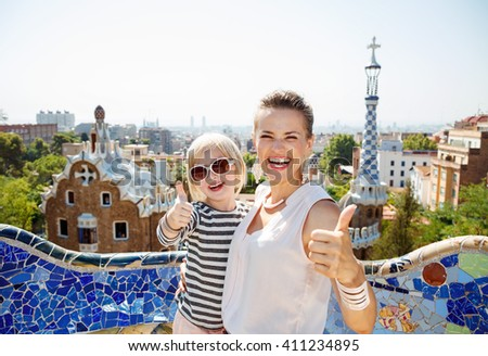 Barcelona will show you how to remarkably spend holiday. Smiling mother and baby at Park Guell showing thumbs up - stock photo