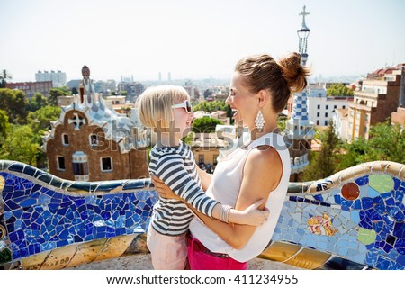 Barcelona will show you how to remarkably spend holiday. Smiling mother and baby having fun time at Park Guell - stock photo