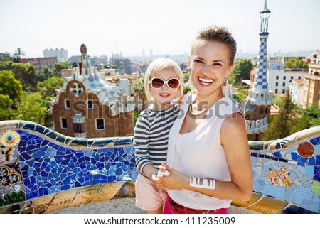 Barcelona will show you how to remarkably spend holiday. Smiling mother and baby spending fun time at Park Guell - stock photo