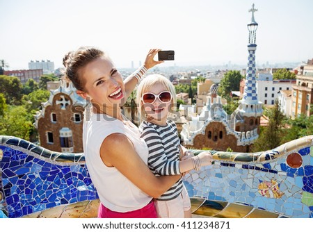 Barcelona will show you how to remarkably spend holiday. Smiling mother and baby taking photos with digital camera at Park Guell - stock photo