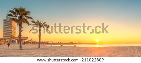 Barceloneta Beach in Barcelona with colorful sky at sunrise - stock photo
