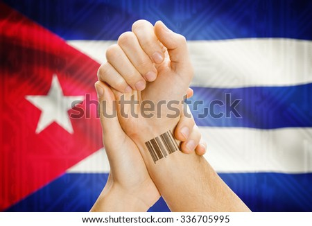 Barcode ID number on wrist of a human and national flag on background - Cuba