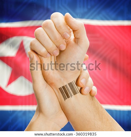 Barcode ID number on wrist of a human and national flag on background series - North Korea